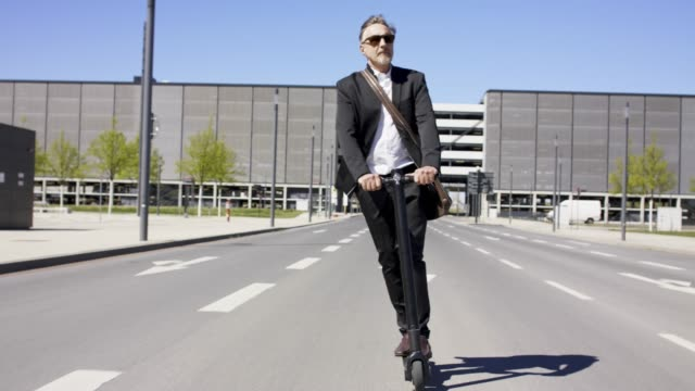 stylish and active senior business man in his 60s in black suit and white shirt is riding his trendy black e-scooter. - mühelosigkeit stock-videos und b-roll-filmmaterial