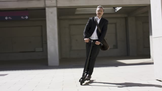 vidéos et rushes de stylish and active senior business man in his 60s is riding his trendy black e-scooter. - agilité entreprise