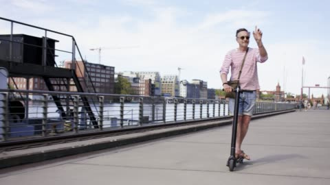 stylish and active senior man in his 60s is riding his trendy black e-scooter in the city of berlin. - active lifestyle stock videos & royalty-free footage