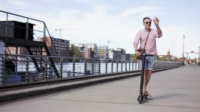 stylish and active senior man in his 60s is riding his trendy black e-scooter in the city of berlin. - push scooter stock videos and b-roll footage