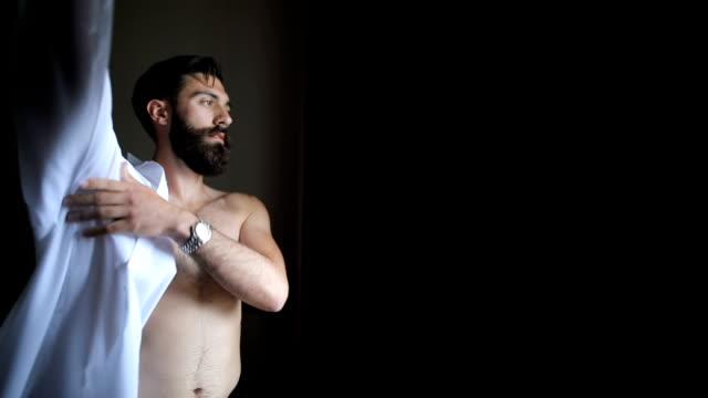 vídeos de stock e filmes b-roll de stylish and elegance. handsome young man dressing up white shirt - homens pelados