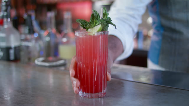 stylish bartender in trendy bar serves healthy, red, non alcoholic cocktail drink - decorated with fresh organic mint leaves and a slice of lime. - tropical cocktail stock videos & royalty-free footage
