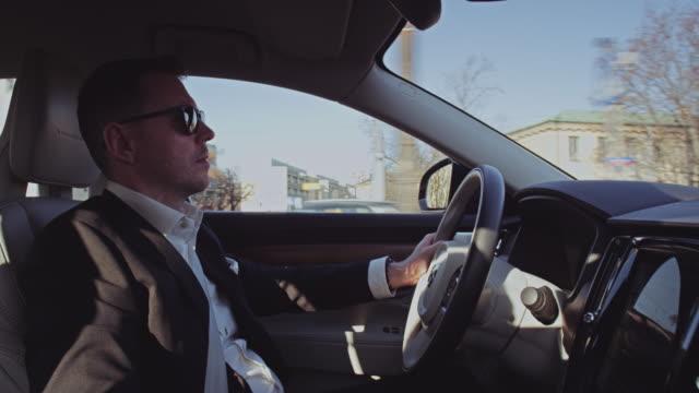 snygg affärsman som kör genom stadens centrum. autonomos bil interiör - profil sedd från sidan bildbanksvideor och videomaterial från bakom kulisserna