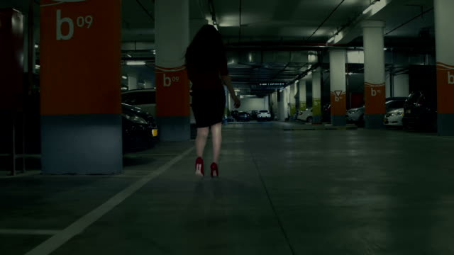 stylish businesswoman walking hastily along the underground parking lot - car park stock videos & royalty-free footage