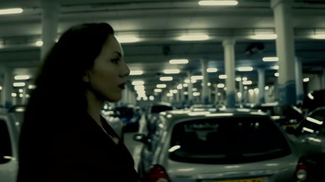vídeos y material grabado en eventos de stock de elegante mujer de negocios caminando precipitadamente en el estacionamiento subterráneo - borde