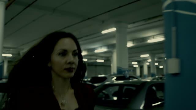vídeos de stock e filmes b-roll de elegante empresária andar apressadamente ao longo do parque de estacionamento subterrâneo - profile