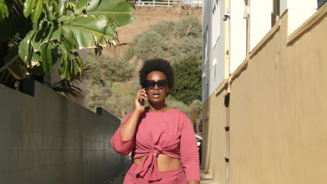 stylish curvy woman talking on cell phone outdoors - body positive stock videos & royalty-free footage