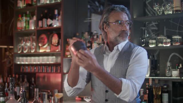 vídeos y material grabado en eventos de stock de stylish, handsome bartender and owner of his own trendy, moody, city bar in his early 50s  - preparing / shaking a cocktail. - propietario