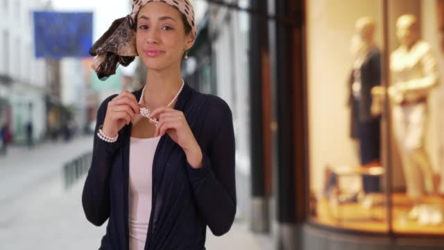 stylish latin female plays with pearl necklace on urban street smiling at camera - トルソー点の映像素材/bロール