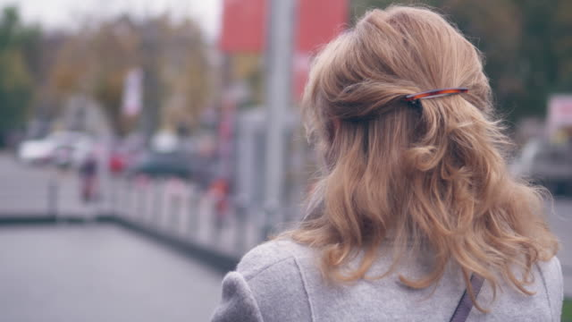 elegante donna matura che parla al telefono mentre cammina per strada - capelli biondi video stock e b–roll