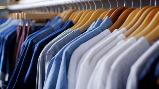 Stylish shirts and pants hang from racks in modern clothing store
