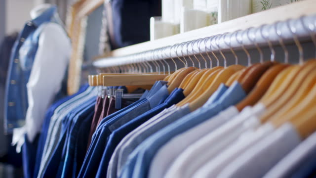 stylish shirts and pants on display in modern clothing store - product variation stock videos & royalty-free footage