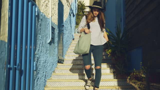 elegant kvinna som utforskar medelhavsstaden. gå nerför trappan - kullersten bildbanksvideor och videomaterial från bakom kulisserna