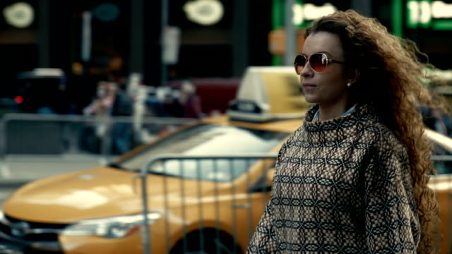 Stylish woman in sunglasses walking along New York street