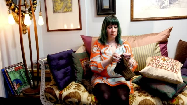a stylish woman knits in her apartment. - stricken stock-videos und b-roll-filmmaterial