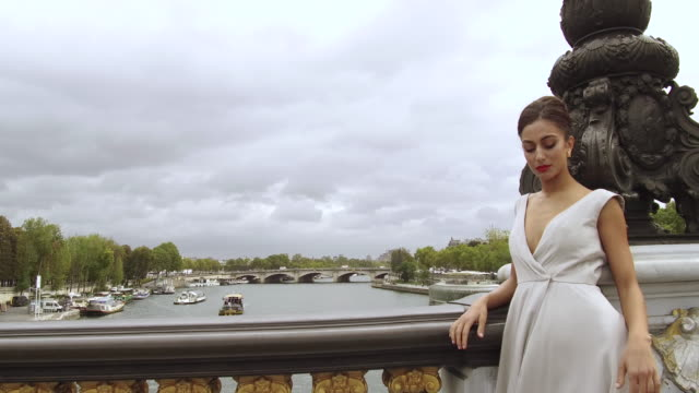 stylish woman leaning on railing of bridge in paris france looking out over the seine river, daytime - pont alexandre iii stock videos & royalty-free footage