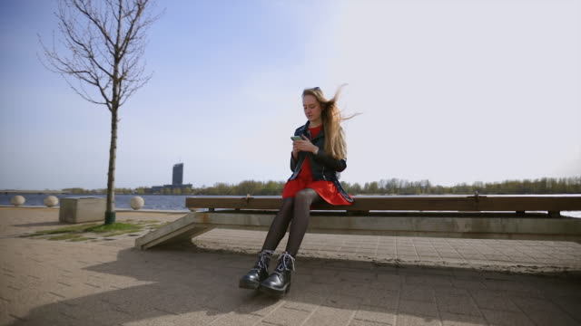 vidéos et rushes de stylish woman sits on bench and uses mobile phone - seulement des jeunes femmes
