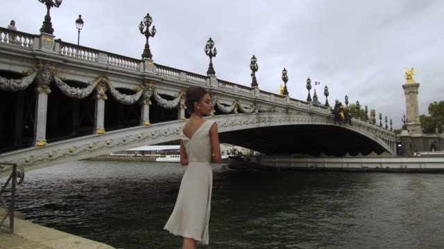 stylish woman standing next to seine river in front of bridge in paris france, daytime - pont alexandre iii stock videos & royalty-free footage