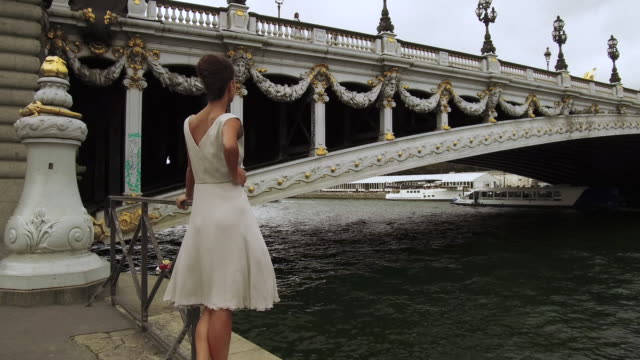 stylish woman standing next to seine river in front of bridge in paris france, daytime - hold me tight stock videos & royalty-free footage