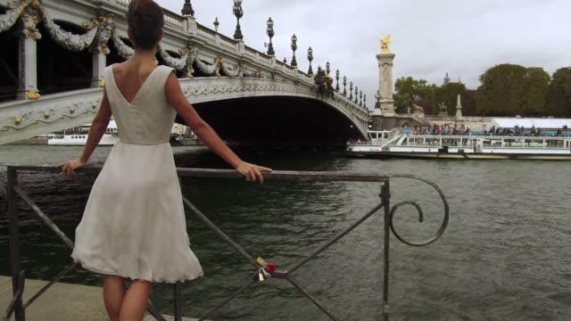 stylish woman standing next to seine river in front of bridge in paris france, daytime - アレクサンドル3世橋点の映像素材/bロール