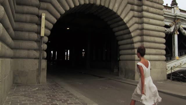 stylish woman walking next to seine river under bridge in paris france, daytime - pont alexandre iii stock videos & royalty-free footage