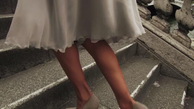vidéos et rushes de stylish woman walking  up steps next to seine river in paris france, daytime - jambe