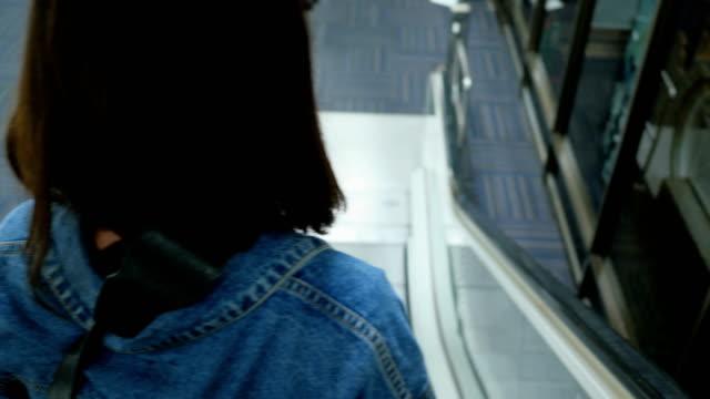 vídeos y material grabado en eventos de stock de mujeres con estilo con la situación de la maleta en las escaleras mecánicas. - maleta