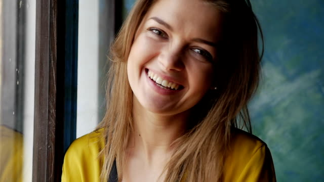 stylish young brunette laughing while posing at the camera next to the window - blouse stock videos & royalty-free footage