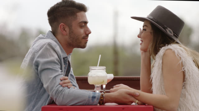 stylish young couple hold hands and chat over cocktails on outdoor patio. - holding hands stock videos & royalty-free footage