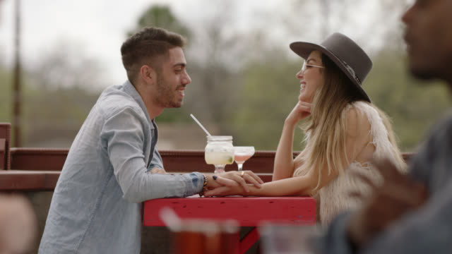 stylish young couple hold hands and laugh over cocktails on outdoor patio. - beatnik stock videos & royalty-free footage