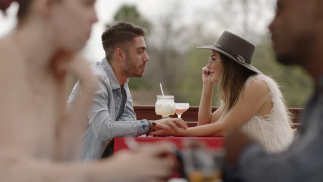 stylish young couple sip cocktails and chat on outdoor bar patio. - beatnik stock videos & royalty-free footage