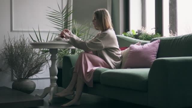 vidéos et rushes de élégante jeune femme prenant son petit déjeuner tout en sms sur le téléphone - pull