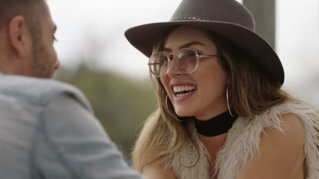 stylish young woman laughs and chats with her date on outdoor patio at happy hour. - sunglasses stock videos & royalty-free footage