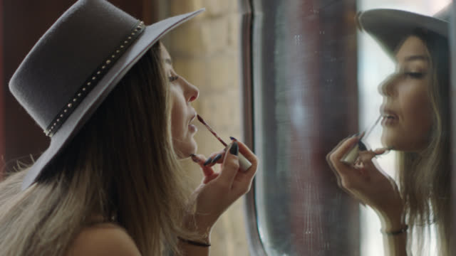 vídeos de stock, filmes e b-roll de stylish young woman touches up makeup with lip brush in mirror of austin bar. - lápis de lábio