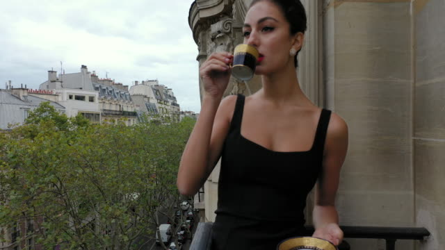 stylish young women drinking coffee on her balcony in paris france, daytime - drinking stock videos & royalty-free footage