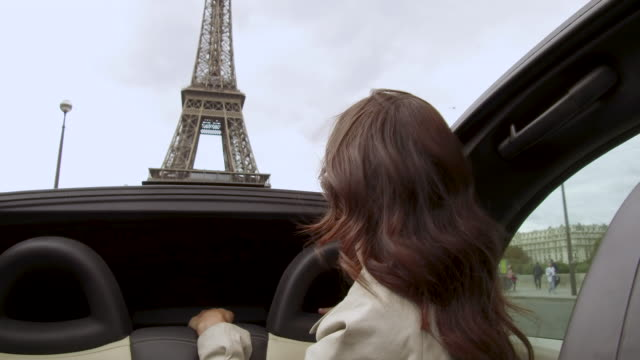 stylish young women in back seat of car as she drives past eiffel tower, daytime - passenger seat stock videos & royalty-free footage