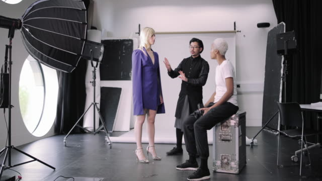 stylist getting model ready on a photoshoot - fashion industry stock videos & royalty-free footage