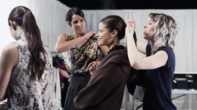 ms stylist making final adjustments on female models hair backstage at fashion show  - fashion show stock videos & royalty-free footage