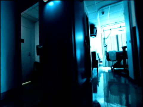 stylized shot from perspective of patient on hospital trolley being wheeled down hospital corridor past doorway revealing empty hospital rooms - patient journey stock videos & royalty-free footage