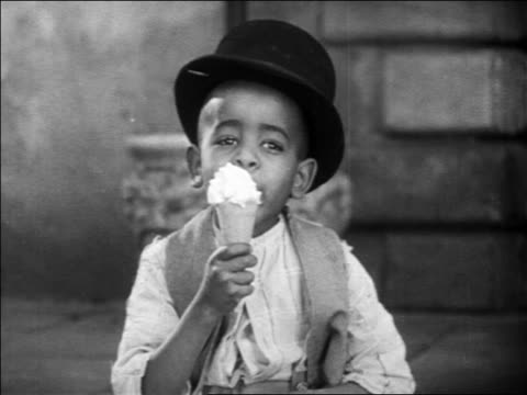 B/W 1931 Stymie from Our Gang in top hat sitting outdoors eating ice cream cone / feature