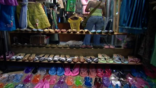 suan lum night bazaar. tilt-up to an arab woman looking at clothes in a stall from a colorful display of slippers. the suan lum market closed in 2011... - salesman stock videos & royalty-free footage
