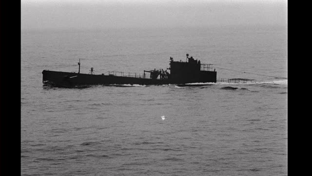 submarine rising out of the water, men run out onto deck and fire the deck gun. submarine rising out of the water on january 01, 1942 - submarine stock videos & royalty-free footage