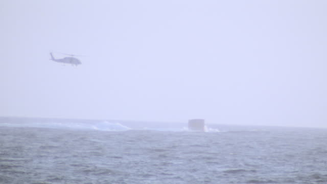 a submarine surfaces on the open sea as a helicopter flies overhead. - surfacing stock videos & royalty-free footage