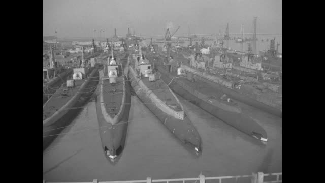 7 subs moored together at dock bow out / POV from bridge traffic passes the subs lashed together at the dock / interior control room officer sticks...