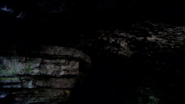 a subterranean stream flows beneath granite outcroppings. - sottosuolo video stock e b–roll
