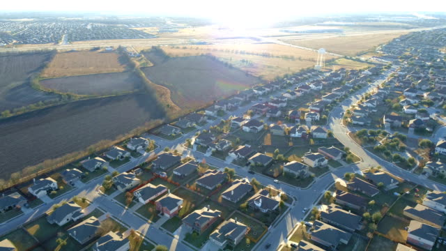 Suburb Neighborhood with Sunflare or Lens Flare Effect at Sunset with Thousands of Homes from Drone view