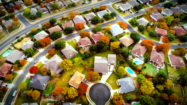 suburb real estate neighborhood colorful rooftops looking down from drone view - modern rock stock videos & royalty-free footage