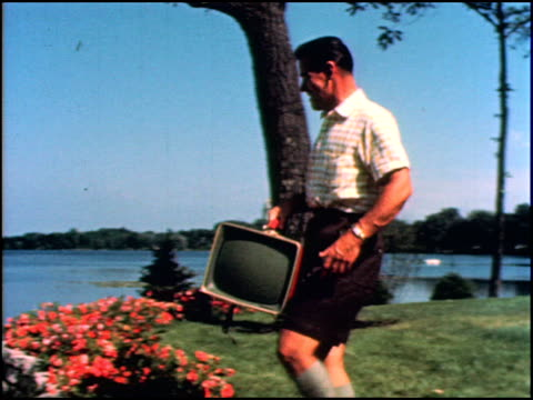 WS suburban dad carries new portable red TV out to the patio on the lake front He sets it on a rock as his wife young son and a neighbor crowd around...