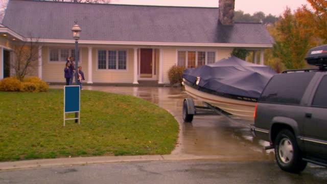 suburban driving away - モーターボート点の映像素材/bロール