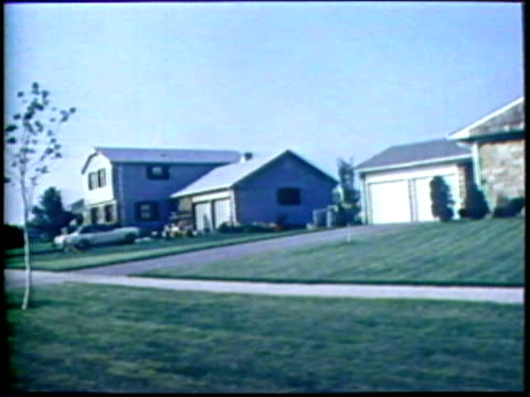 1973 pov ws suburban homes with neat lawns/ usa/ audio - suburban stock videos and b-roll footage